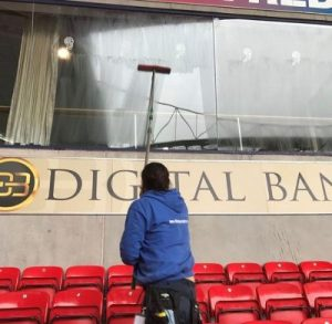 Picture of an employee cleaning a window of a box at a football stadium. Ultra Cleaning Service can provide regular maintenance cleaning solutions.