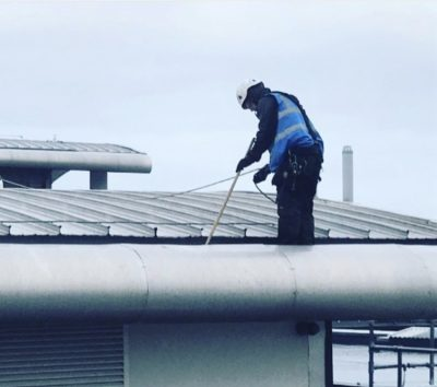 Picture of a Ultra Cleaning Service employee cleaning an industrial gutter. INtroducing Ultra Cleaning Services gutter cleaning