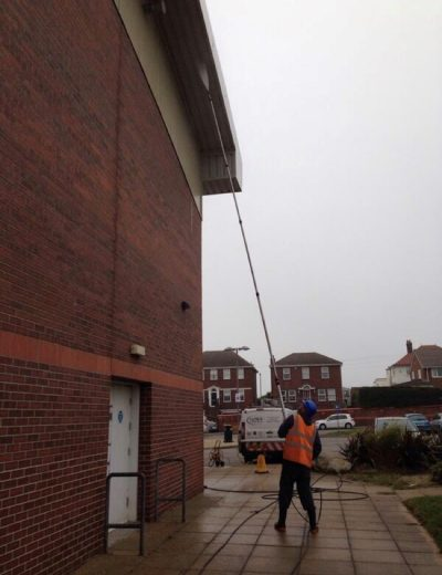 A picture of a member of the team cleaning a building. Ultra Cleaning Services provide jet washing and soft washing solutions to clean your whole building.