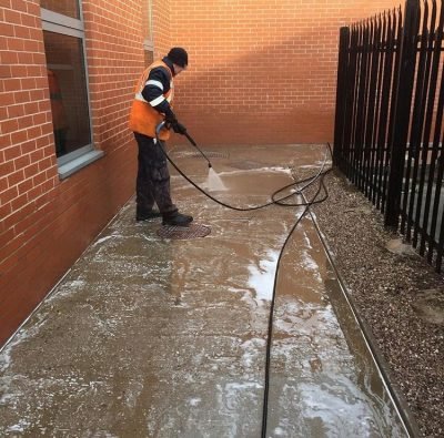 Picture of a member of the Ultra Cleaning Service team power washing a pathway - introducing playground cleaning services.