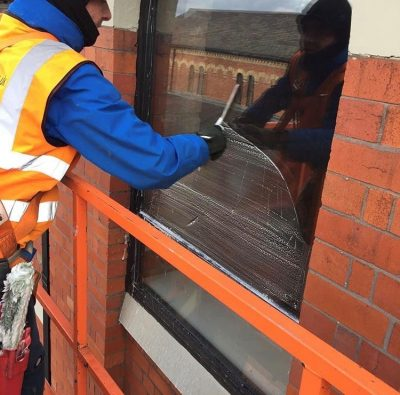 A member of the Ultra Cleaning Service team cleaning a window with a squeegee - introducing Ultra Cleaning Service's window cleaning solutions