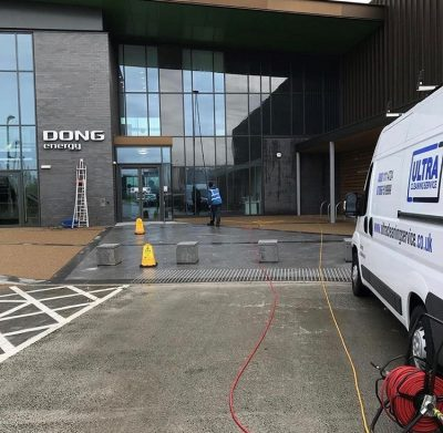 Picture of an ultra cleaning service employee cleaning the front on a prestigous office using reach and wash technology. Introducing Ultra Cleaning Service Commercial Window Cleaning